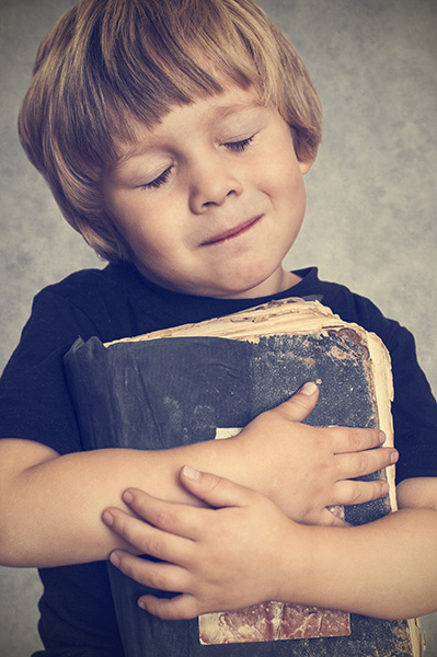 boy hugging an old book